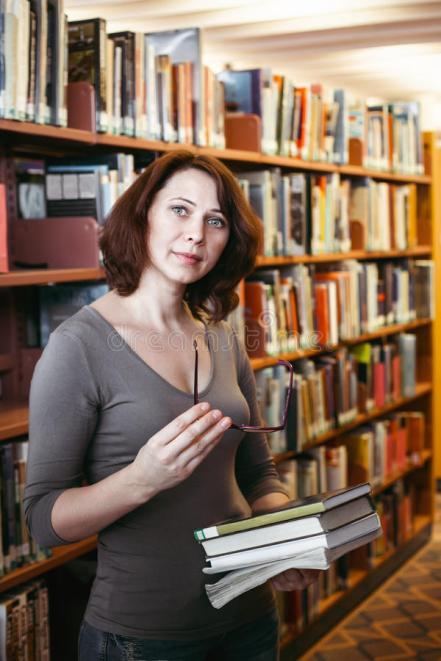 middle-age-woman-library-portrait-mature-brunette-caucasian-student-glasses-holding-book-looking-directly-camera-70641943