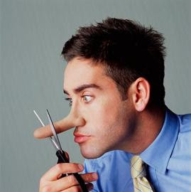 Young man cutting nose with scissors, side view, close-up