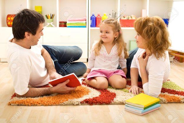 12477084-la-hora-del-cuento-familia-feliz-con-un-ni-o-leyendo-un-libro-tirado-en-el-suelo-foto-de-archivo
