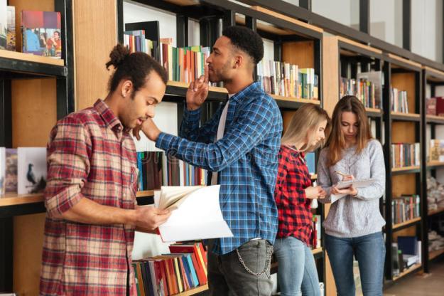 estudiantes-serios-jovenes-de-los-hombres-que-se-colocan-en-libros-de-lectura-de-la-biblioteca-93534517