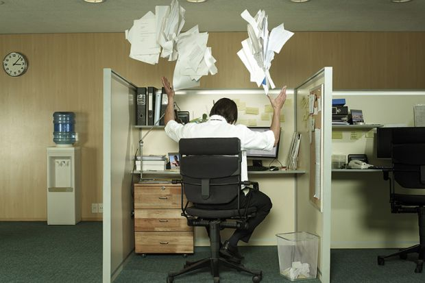 man-at-desk-throwing-papers-in-the-air