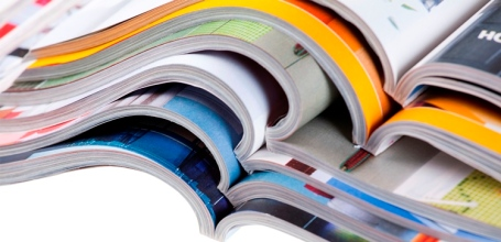 Pile of colour illustrated magazines on white background. Isolated.