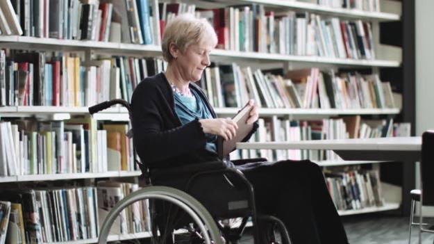 715107168-professeur-duniversite-chaise-roulante-handicap-bibliotheque