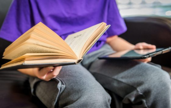 Boy holds old book and tablet