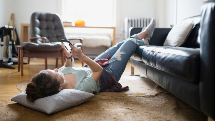 Woman laying with feet up texting cell phone