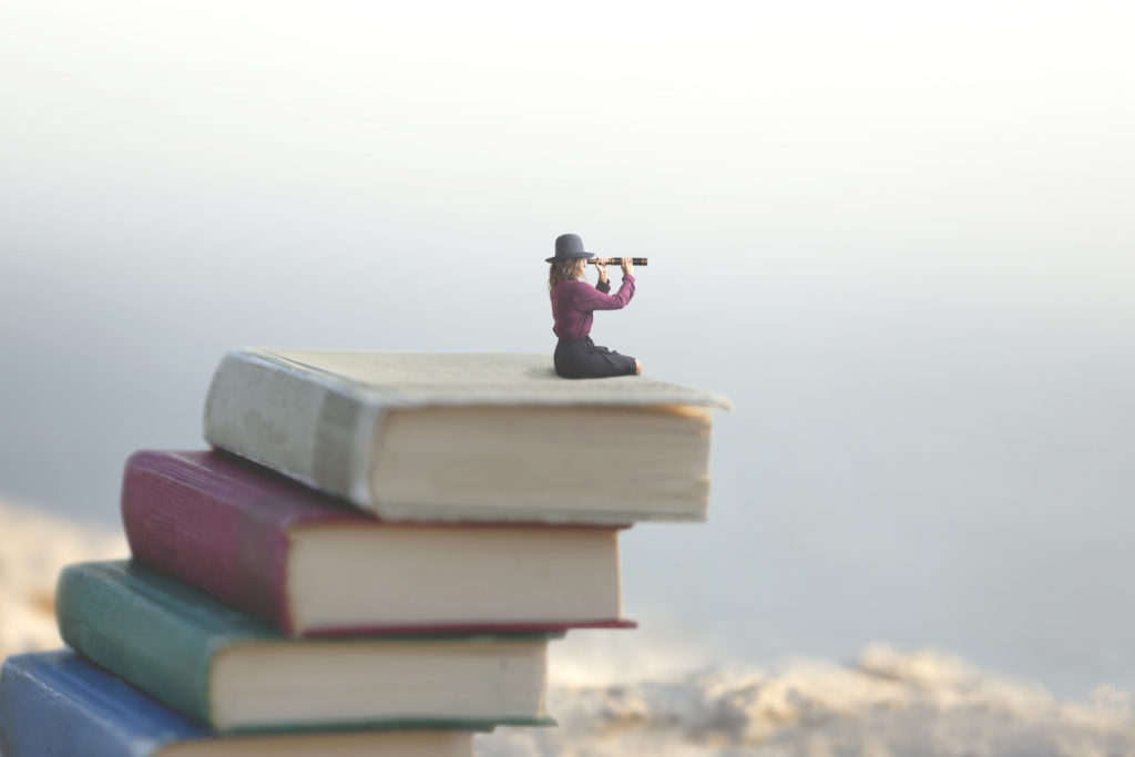 miniature woman looks at the infinity with the spyglass on a scale of books
