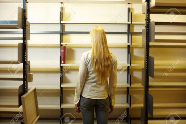 5934882-estudiante-mirando-estantes-vacc3ados-de-libro-en-la-biblioteca